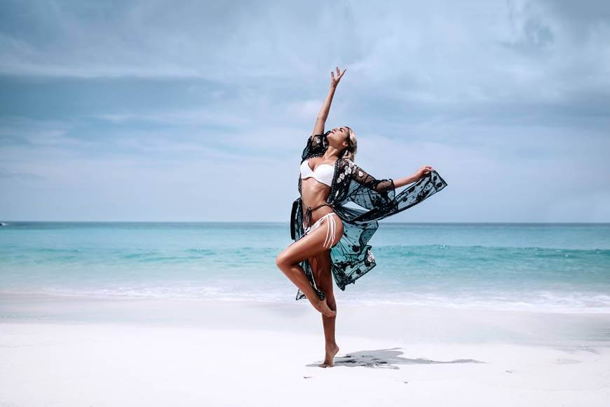 devojka u kupacem kostimu igra na plazi
