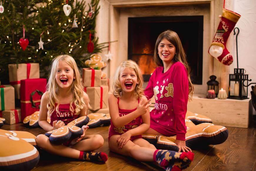 Deca u novogodišnjim pidžama se smeju ispred jelke