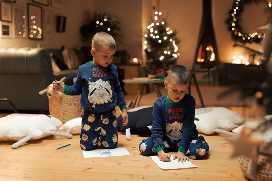 Dva dečaka u novogodišnjoj pidžami crtaju na papiru