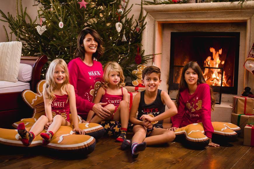 Žena sedi sa decom ispred jelke u pidžami