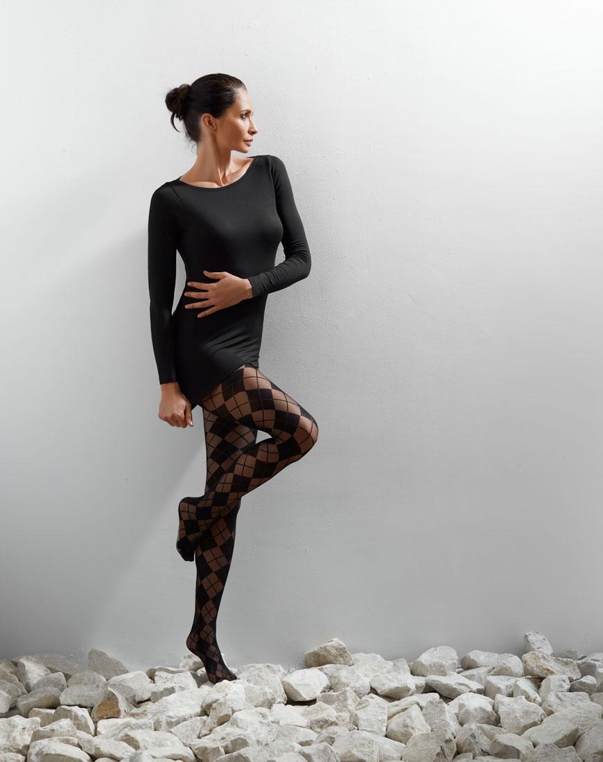 Žena stoji na kamenju u čipkastim čarapama i haljini do kolena