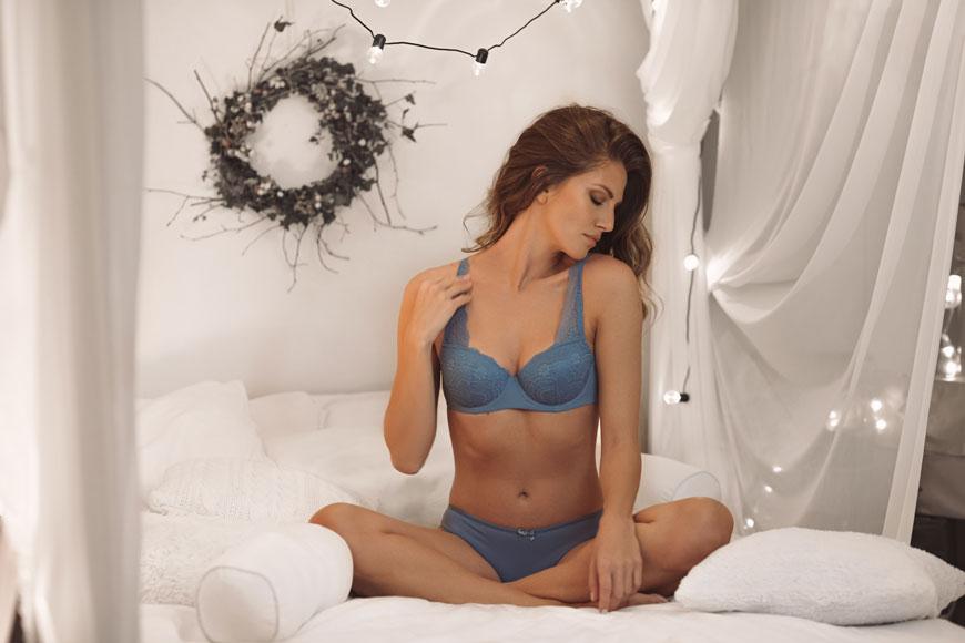 Devojka u plavom donjem vešu na krevetu